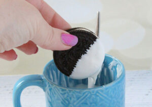a female hand holding an Oreo which has been dipped into the mug below it full of white-candy melt, the Oreo is half covered and some is dripping off
