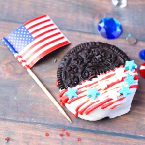image of an Oreo Cookie which has been dipped in white chocolate and drizzled with red candy with star sprinkles added as a 4th of July Treat for kids to make next to a US flag on a wooden table top a few blue, red and white gems are scattered around