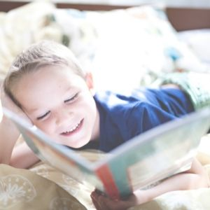 young boy reading on his bed