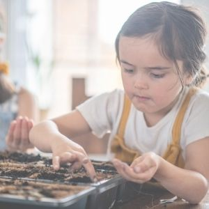 child putting seeds in a seed tray