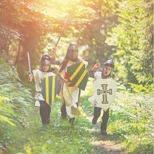 3 kids in the woods playing knights for a history activity