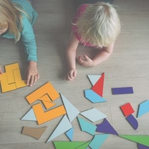 kids laying on the floor playing with shapes in maths