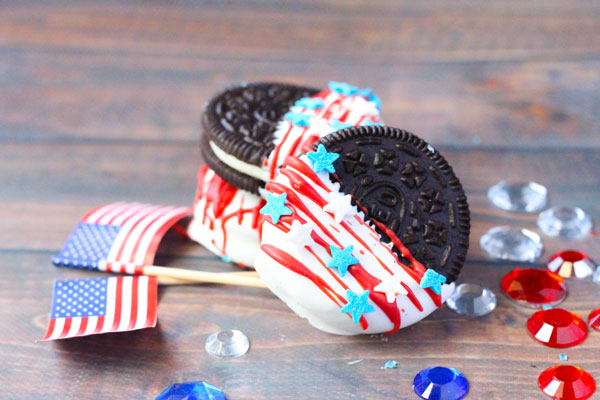 landscape picture of a stack of decorated Oreos for Independence Day, the cookies have been dipped in white-candy melts and drizzled with red then sprinkle stars have been added. These are stacked on a wooden table with mini US flags and red, white and blue gems beside
