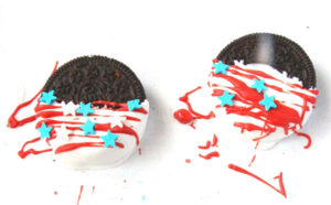 2 Oreo Cookies half dipped in white candy melts with red stripes drizzled on and blue and white star sprinkles placed on top drying on white parchment paper