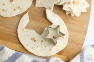 cutting star shapped tortilla chips from flour tortillas