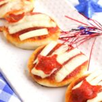 mini pizzas with stripped cheese and pepperoni star on a white plate with a red, white and blue sparkler a simple recipe for the 4th of July to cook with kids