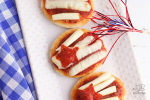 3 mini flag pizzas with cheese string stripes and mini pepperoni star on a white plate with a sparkler laying on a blue gingham cloth