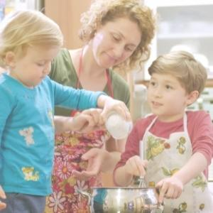 mum cooking with 2 kids wearing an apron, the kids are mixing and pouring ingredients into the bowl
