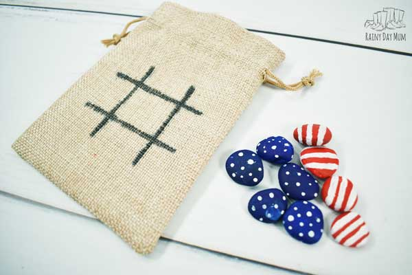 a set of painted pebbles with stars and stripes next to a burlap pouch a quick and easy 4th july game for kids to make and play