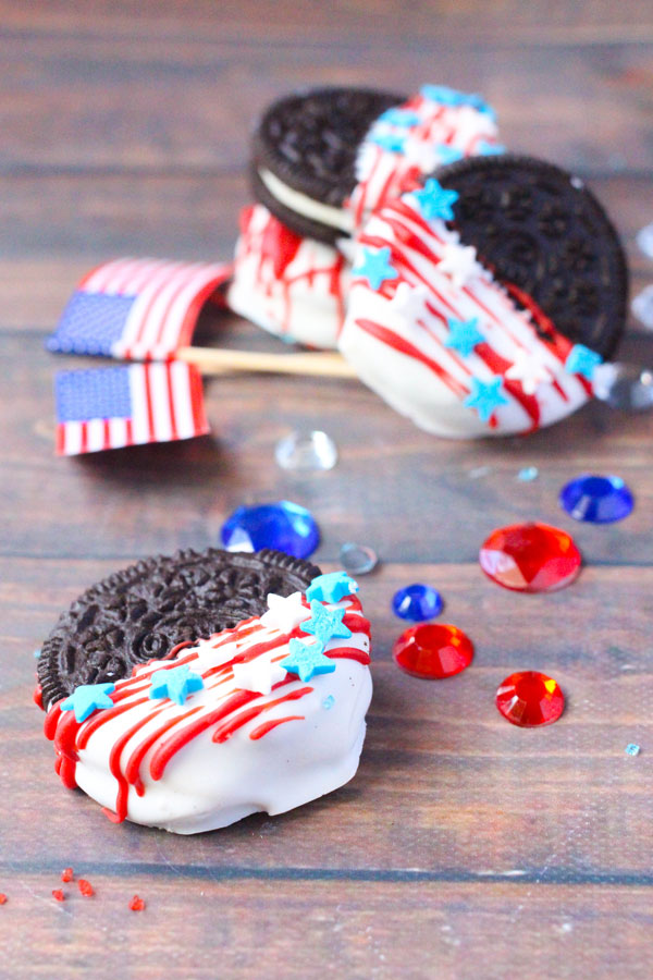 a stack of 4th of July decorated Oreo Cookies in the back ground with USA flag and red and white gems on a wooden table, in the foreground there is a single close up view of one of the Oreos made by kids
