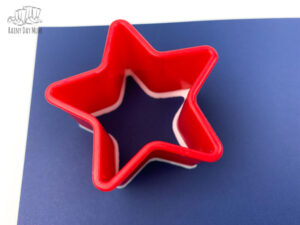 paint coated star cookie cutter printing a star shape on a piece of blue paper