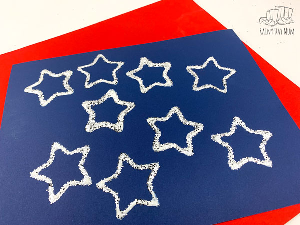 toddler printed stars on a blue paper laid on a red a fun easy craft for 4th of July to make a placemat that is unique for each family member