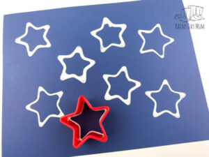 star cookie cutter printing the last star with white paint on a blue paper placemat for a toddler craft for US Independence Day