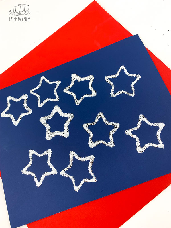 a blu sheet of paper on top of a red sheet the blue paper is printed with white stars by a little kid for a 4th of july craft