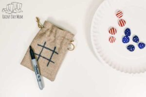 tic tac toe board added to a burlap bag for a quick and easy storage solution for play