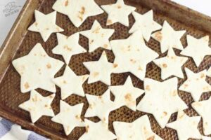 multiple sizes of star shaped tortilla chips on a baking tray sprayed with cooking spray