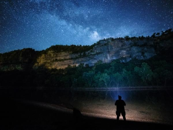 a person standing at the edge of some water with rock wall in front looking up at the night sky