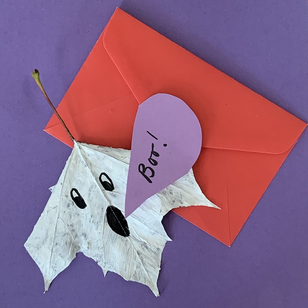 spooky leaf ghost with a paper speech bubble saying boo on a piece of paper with an envelope beside