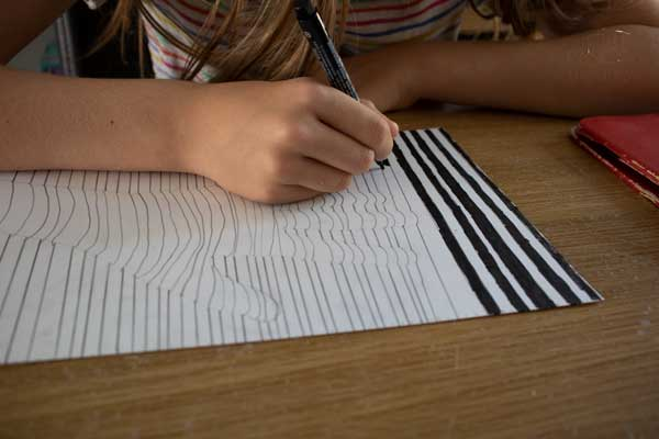colouring every other line of the paper to create the black painting style of Frank Stella
