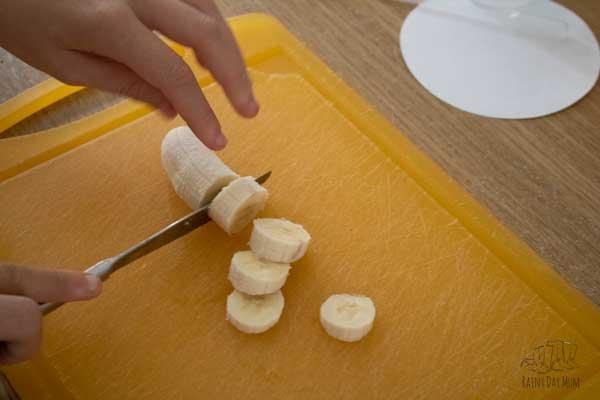 chopping up a banana on a yellow chopping board