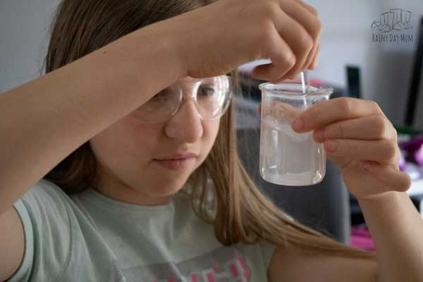 tween girl stiring a beaker of solution to use in an experiment to extract DNA